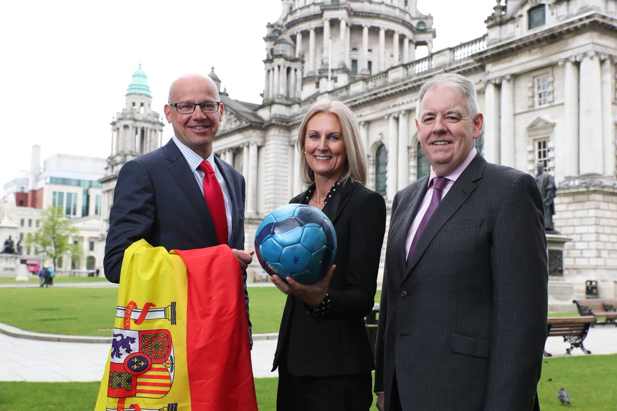 Three people, a woman in the middle holds a football and a man to her left holds a Spanish flag. They are outside, in front of the grand Belfast City Hall.