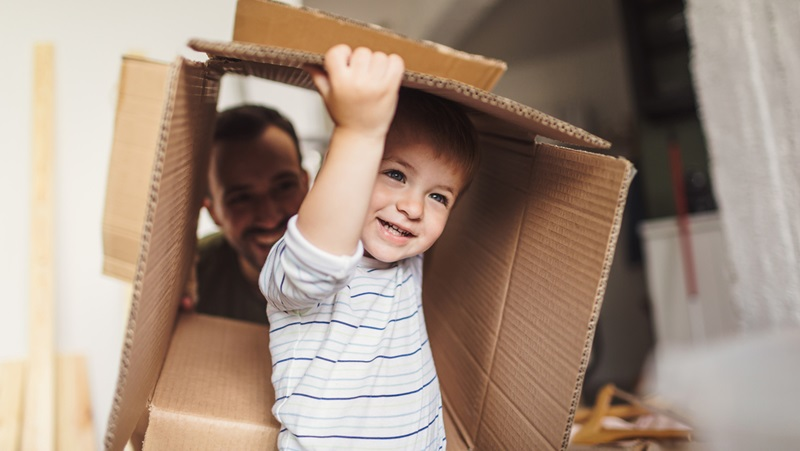 Toddler playing with cardboard box