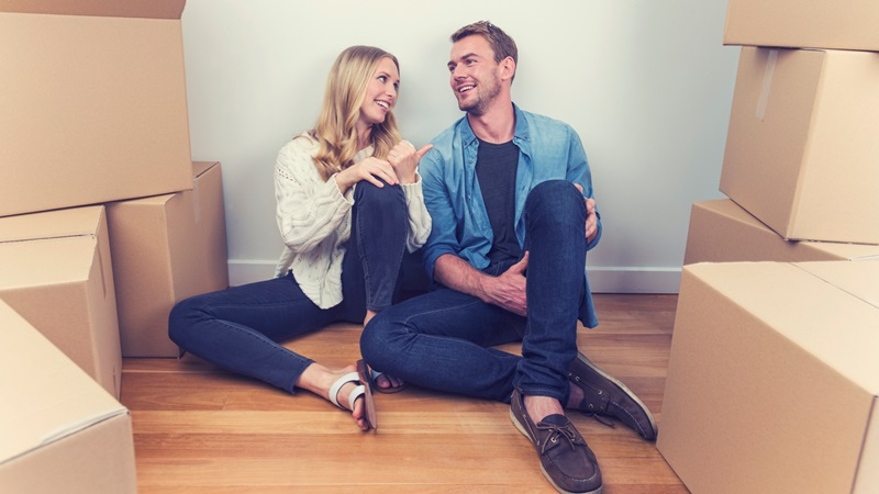 Couple sitting on floor smiling, surrounded by boxes