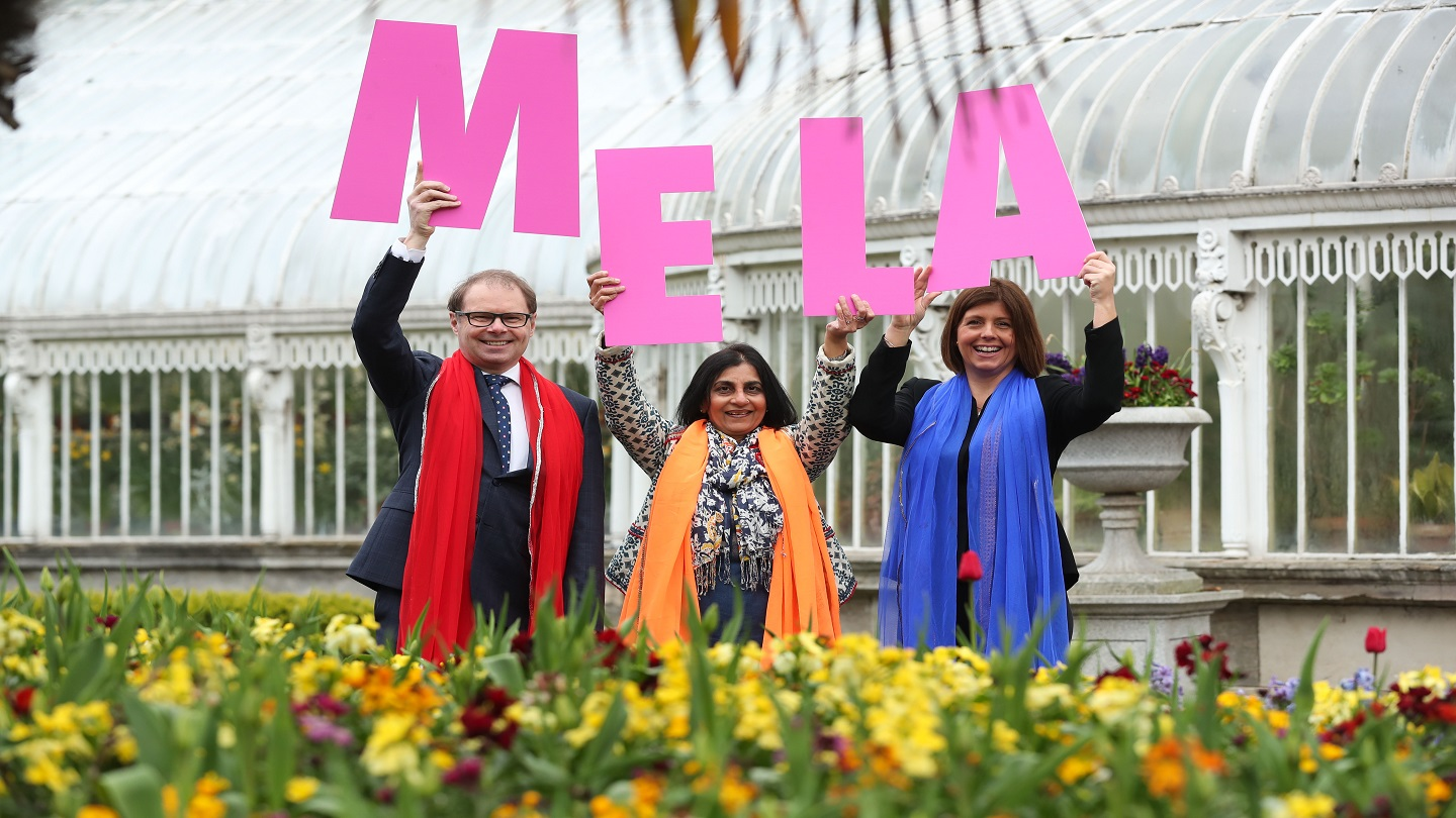Three people stand outside in a botanical garden. They're wearing colourful scarves and holding up large pink letters that spell 'MELA'