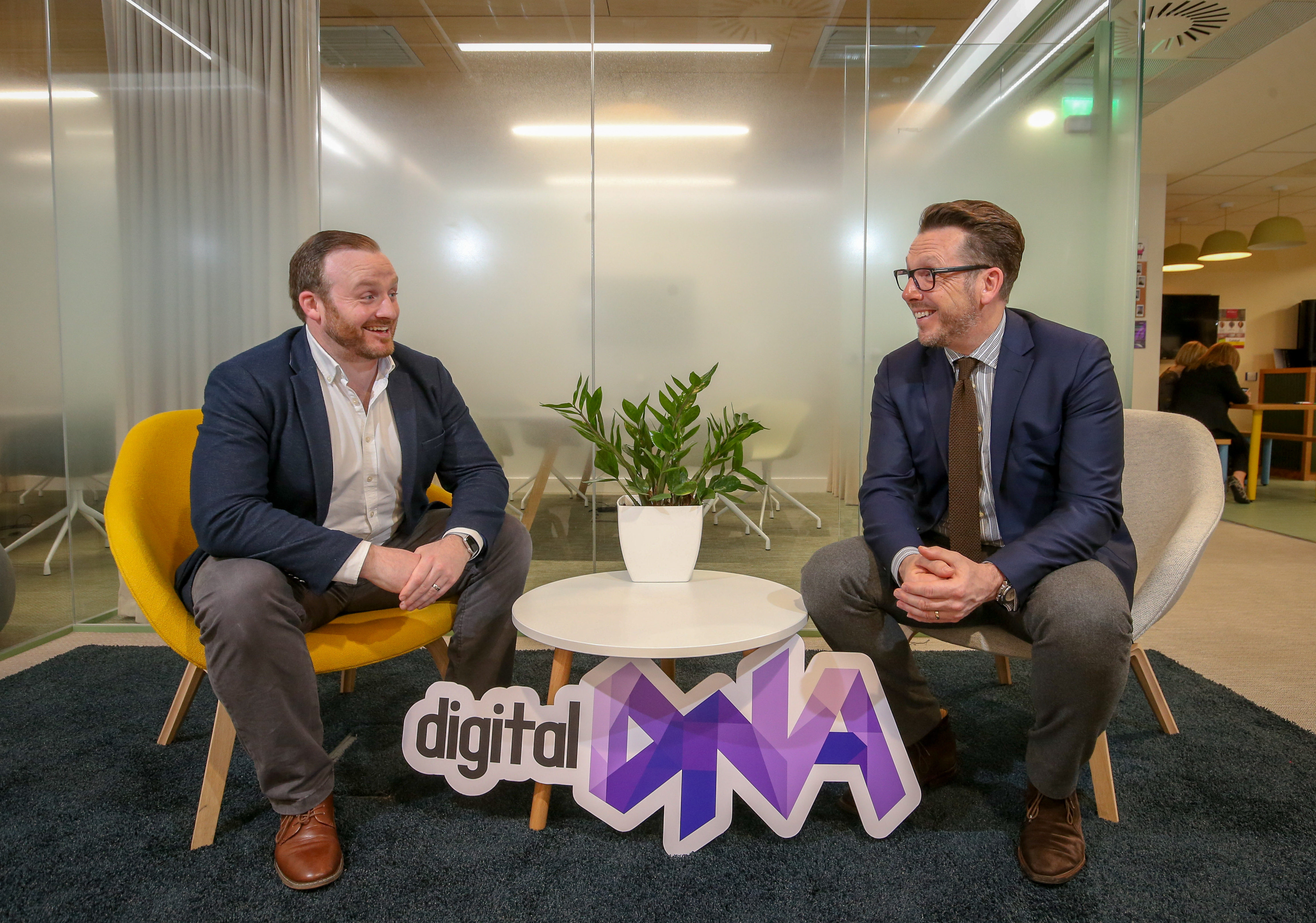Two men in suits sit opposite each other at a coffee table, looking at each other and laughing. a purple 'DIgital DNA' sign sits in front of them.