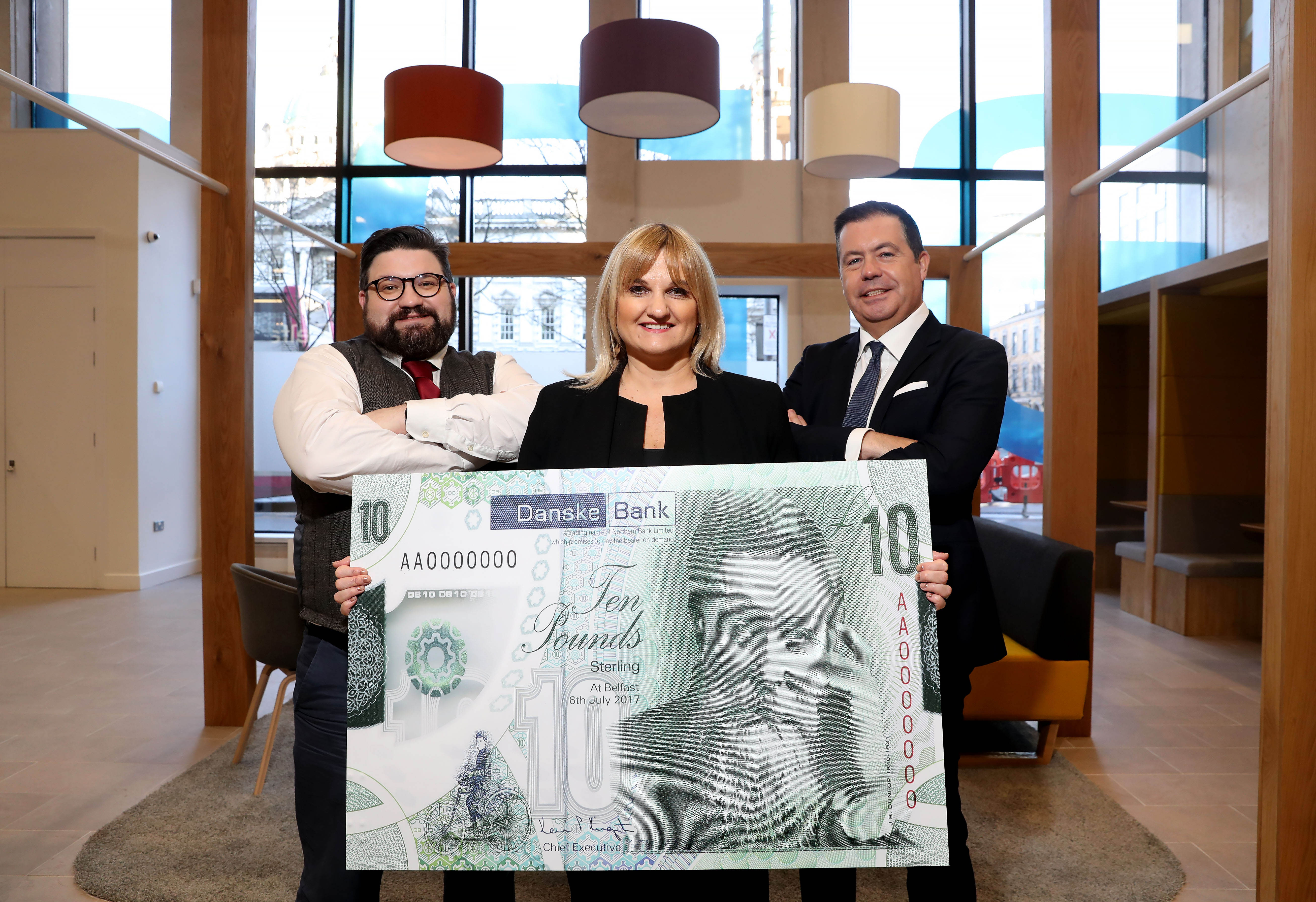 A woman stands between two men holding a large, green Danske Bank £10 note. The two men have their arms folded.