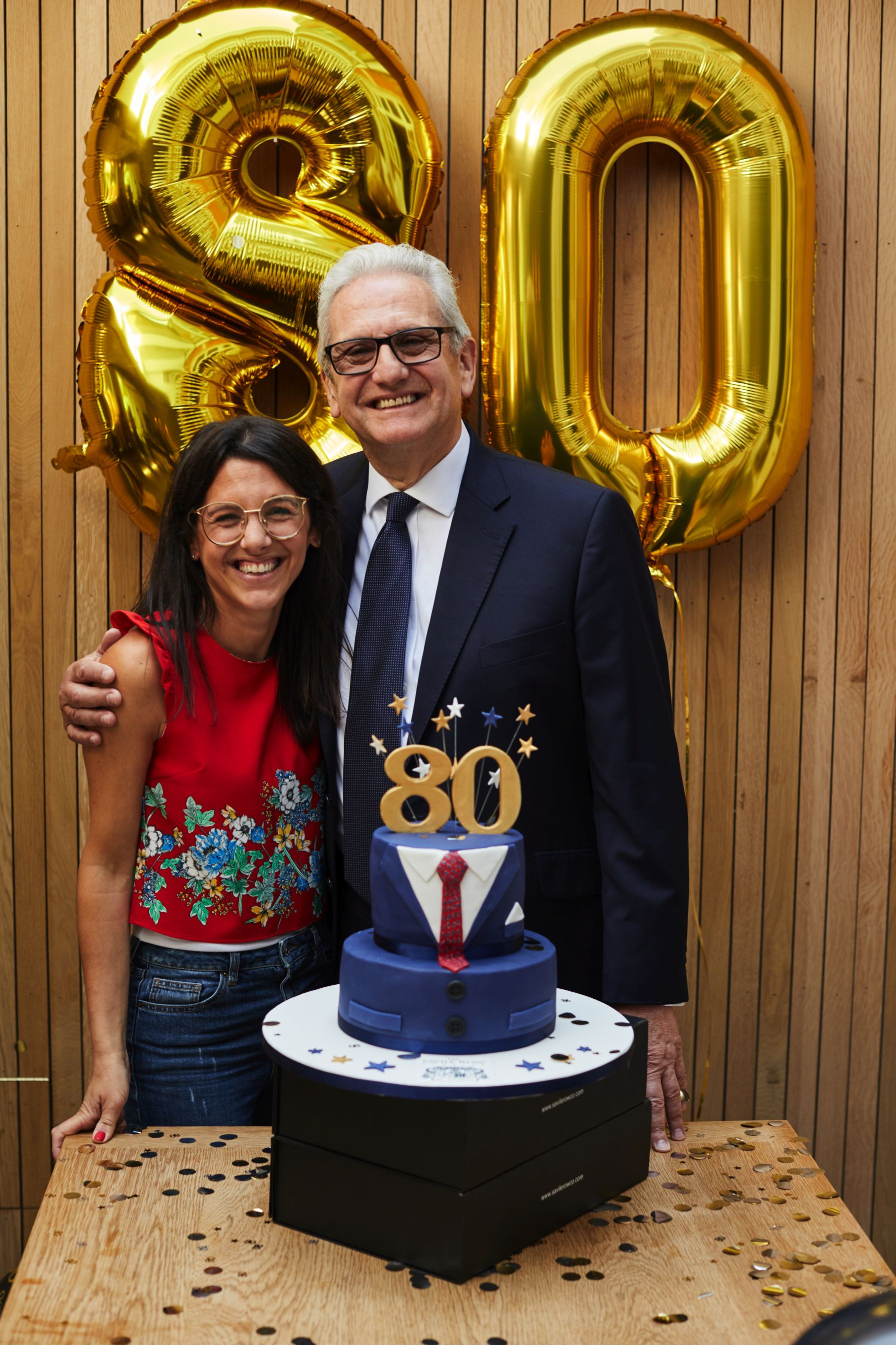 A woman and man stand together side by side smiling widely. There are two big '8' and '0' balloons behind them and a cake decorated like a suit with an '80' on top.