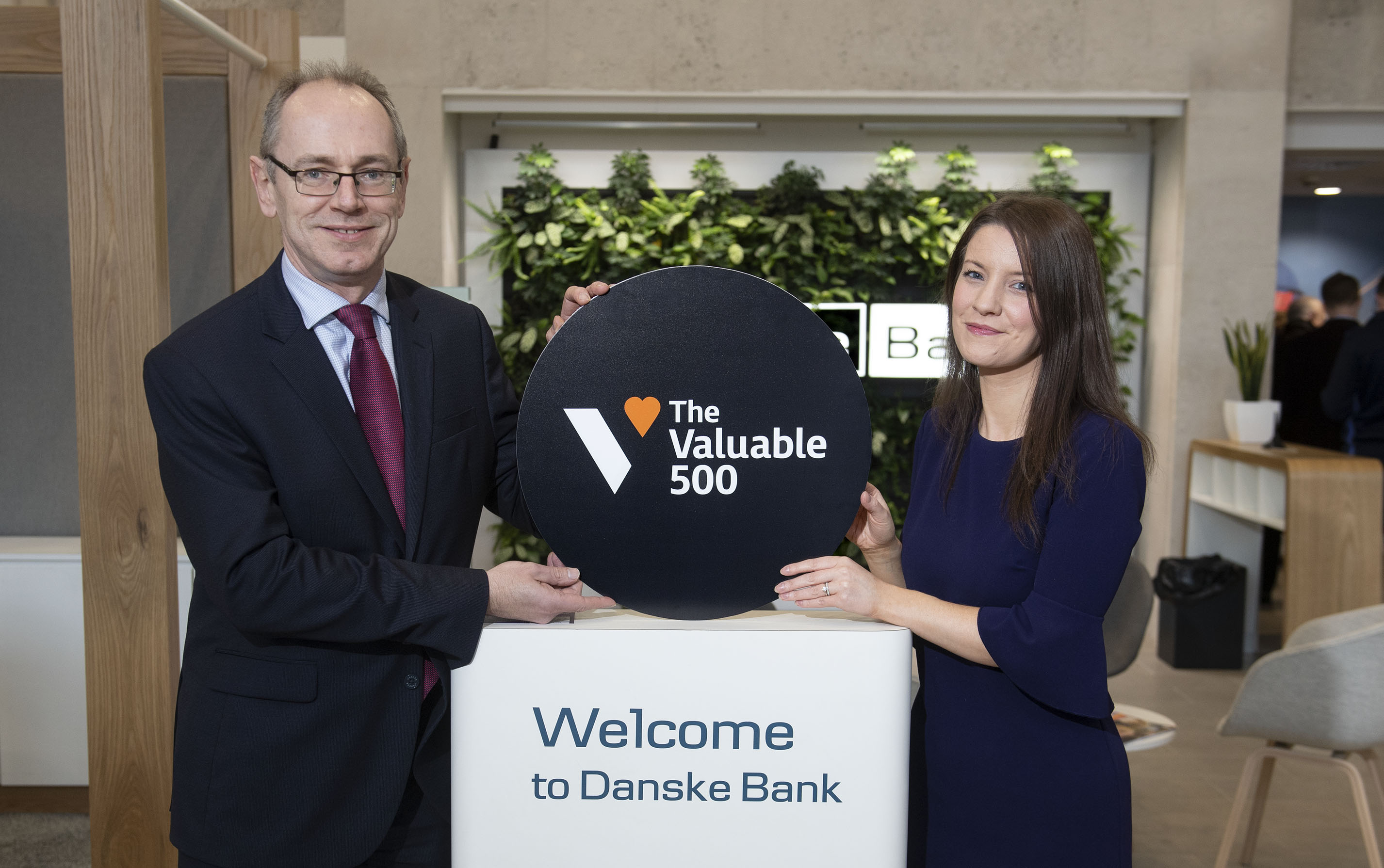A man and woman stand inside. They're holding a circle board that says 'The Vaulable 500' above a stand that says 'Welcome to Danske Bank'.