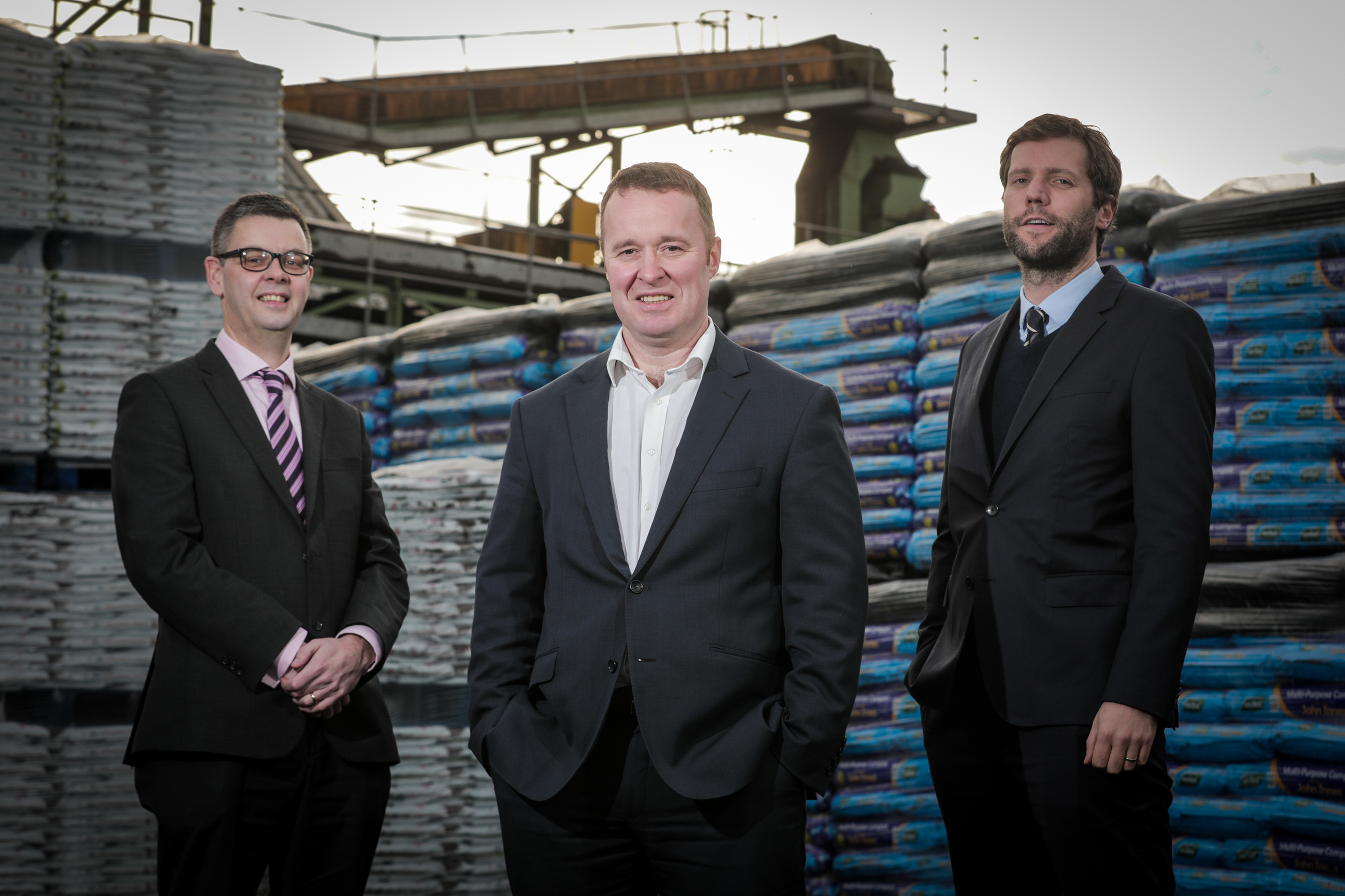 Three men in suits stand, spread out from each other slightly, in a workyard. Behind them is machinery for transporting products and stacks of bags of soil.